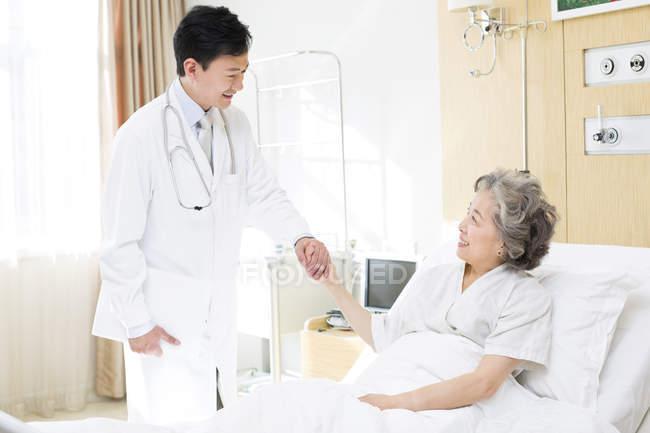 Médico chino cogidos de la mano con el paciente en el hospital - foto de stock