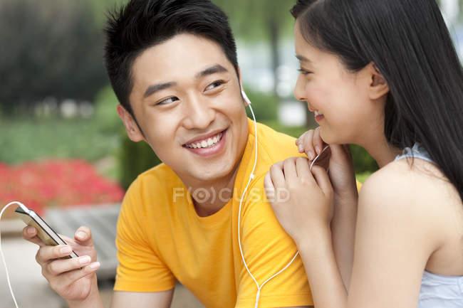 Chinesisches Paar hört Musik auf Smartphone und teilt Kopfhörer im Freien — Stockfoto