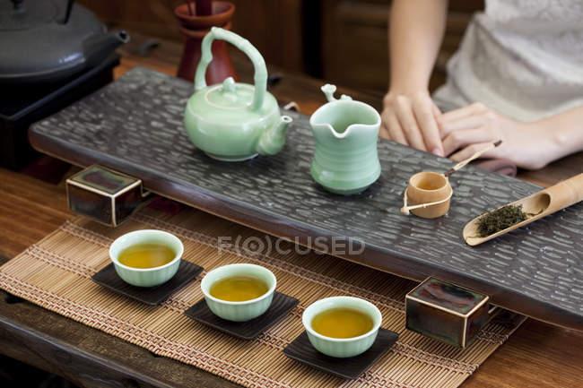 Gros plan sur la cérémonie traditionnelle chinoise du thé et la femme en arrière-plan — Photo de stock