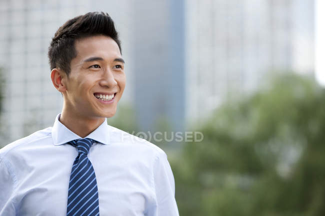 Confident Chinese businessman standing outdoors — Stock Photo