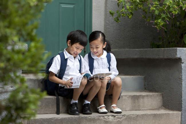 Китайский мальчик и девочка учатся на крыльце — стоковое фото