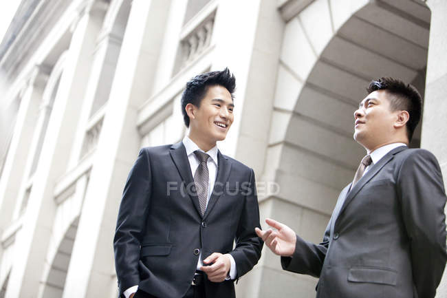 Китайских бизнесменов говорить перед зданием — стоковое фото