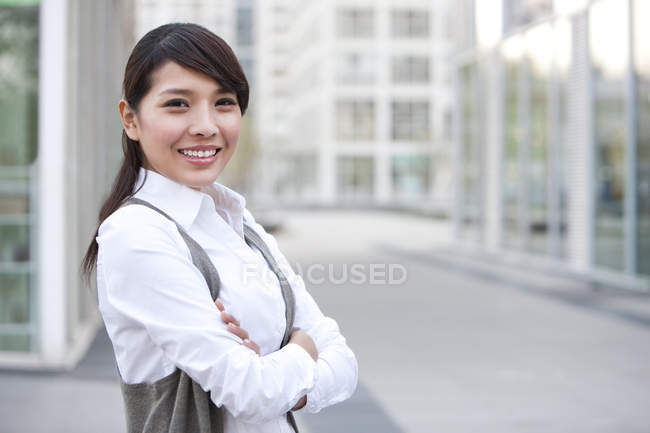 Portrait of Chinese businesswoman with arms crossed on street — Stock Photo