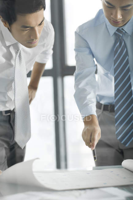 Des hommes d'affaires chinois discutent du plan au bureau — Photo de stock