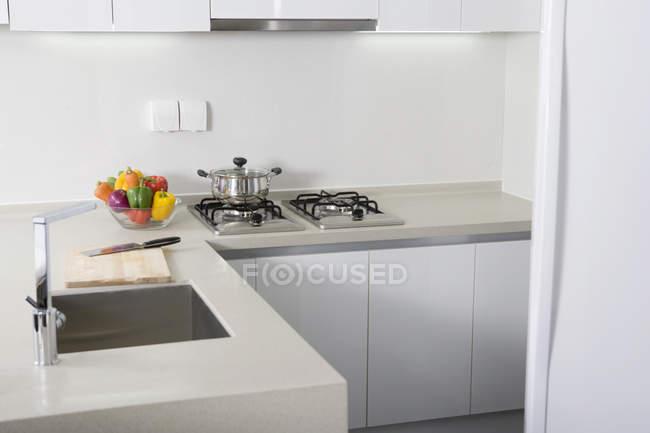 Interior da cozinha moderna com legumes na mesa — Fotografia de Stock