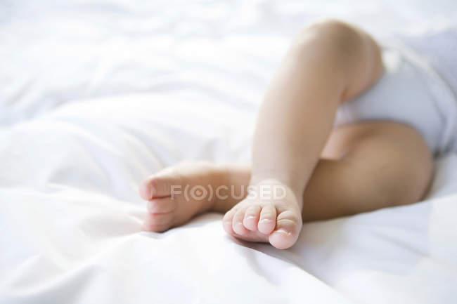 Gros plan des pieds du nourrisson au lit — Photo de stock