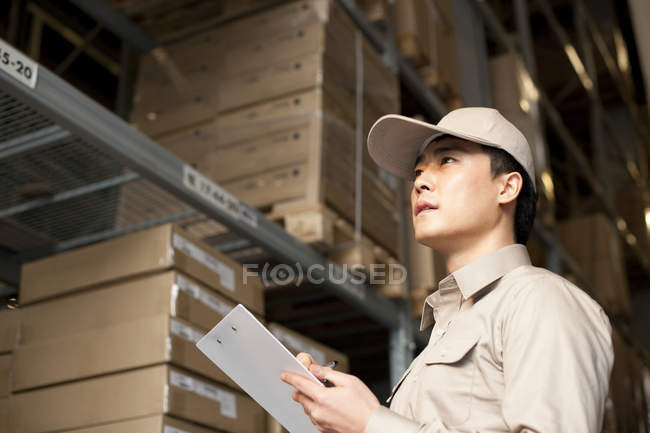 Male Chinese warehouse worker writing with clipboard — Stock Photo