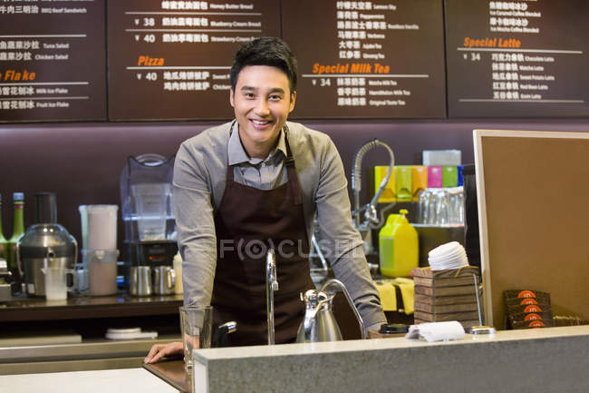 Male Chinese coffee store clerk leaning on counter in cafe — Stock Photo