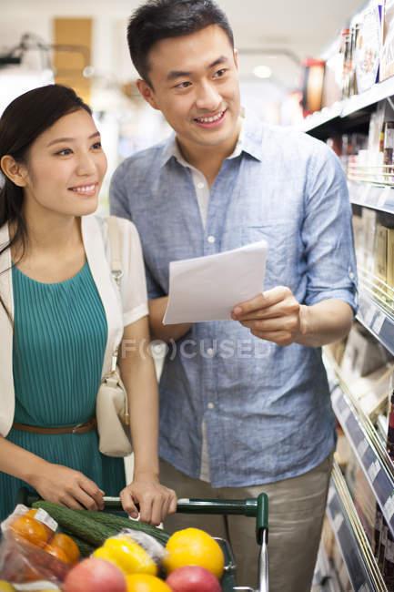 Casal de chineses exploração lista de compras no supermercado — Fotografia de Stock
