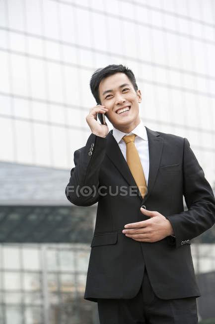 Chinese businessman talking on phone in front of business building — Stock Photo