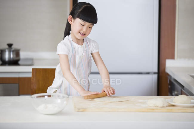 Chinese girl rolling dough on kitchen table — Stock Photo