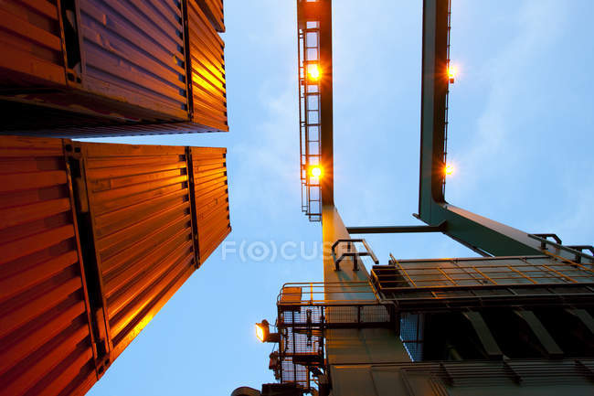 Bottom view of crane and stack of cargo containers — Stock Photo