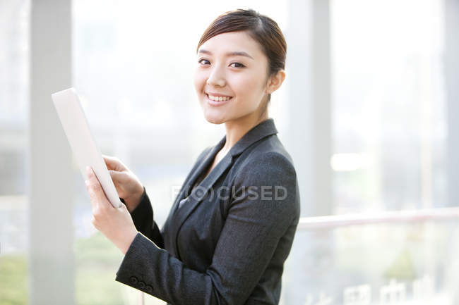 Chinese businesswoman using digital tablet and looking in camera — Stock Photo