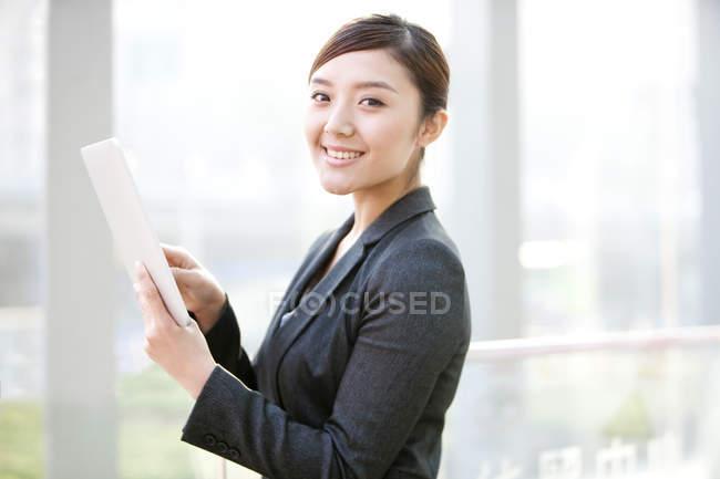 Китайская предпринимательница использует цифровой планшет и смотрит в камеру — стоковое фото