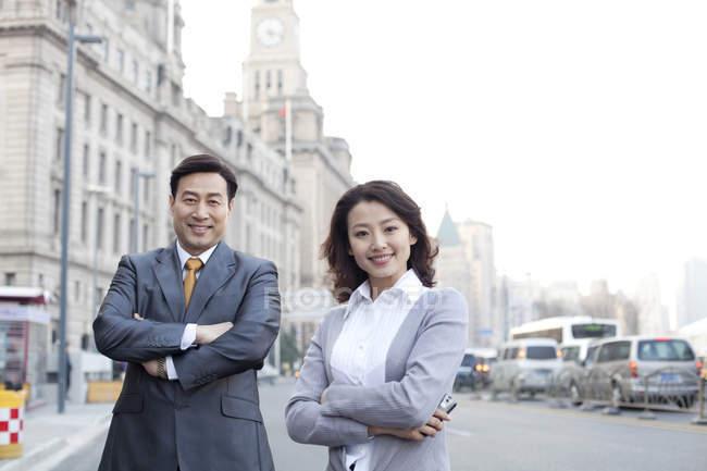 Uomini d'affari cinesi in piedi con le braccia incrociate sulla strada nel distretto finanziario — Foto stock