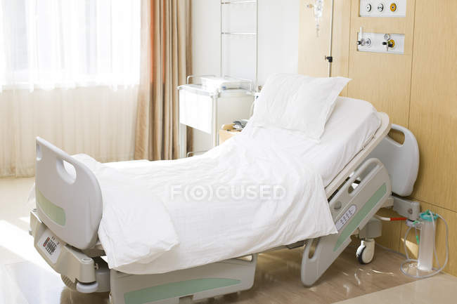 Empty hospital bed in clinic room — Stock Photo
