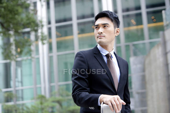 Confident Chinese businessman looking at view in front of office building — Stock Photo