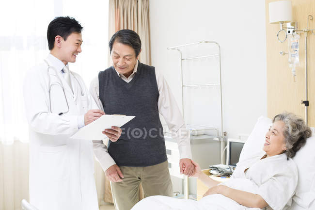Médecin chinois parlant avec couple de personnes âgées à l'hôpital — Photo de stock