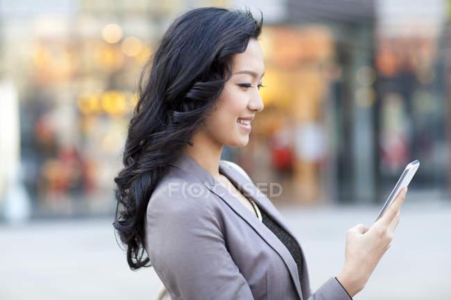 Mulher chinesa usando smartphone na rua da cidade — Fotografia de Stock