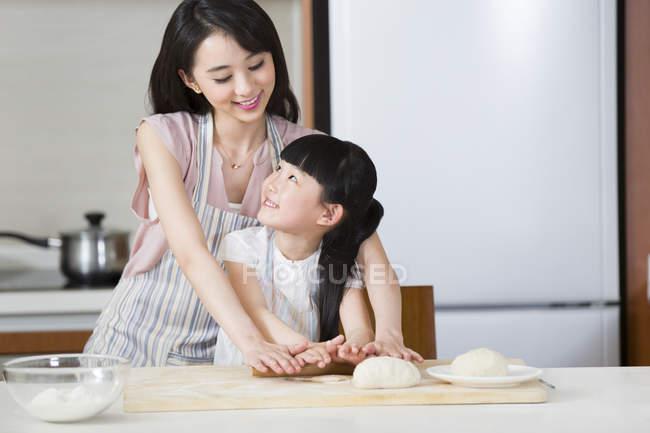 Mère chinoise et fille rouler la pâte dans la cuisine ensemble — Photo de stock