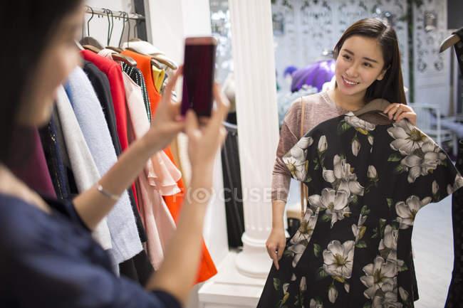 Китайський подруг приміряє плаття і беручи фотографії в магазин одягу — стокове фото