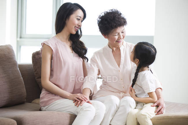Chinese three generations of women sitting and talking on sofa — Stock Photo