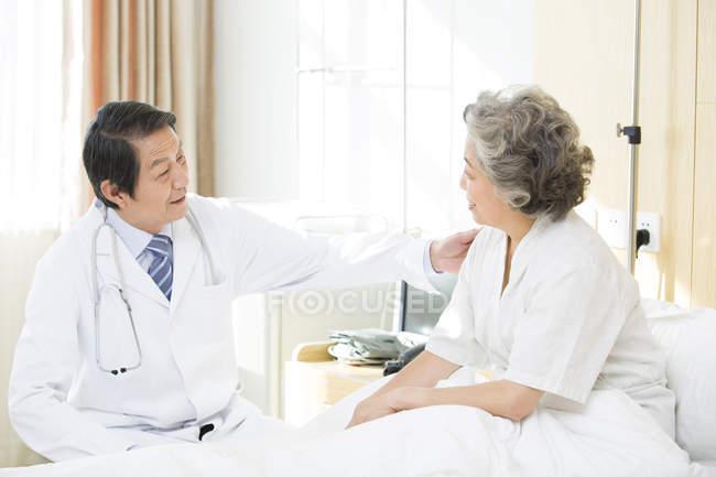 Médico chino que habla con el paciente en el hospital - foto de stock