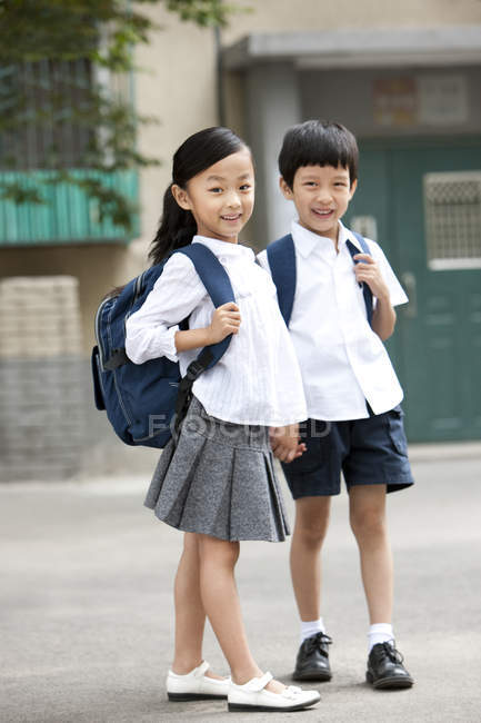 Chinese Children With Backpacks Standing On Street Two People