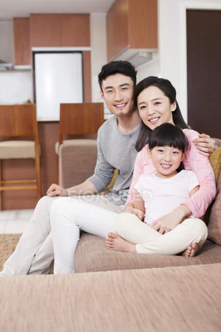 Китайская семья отдыхает на диване и смотрит в камеру — стоковое фото