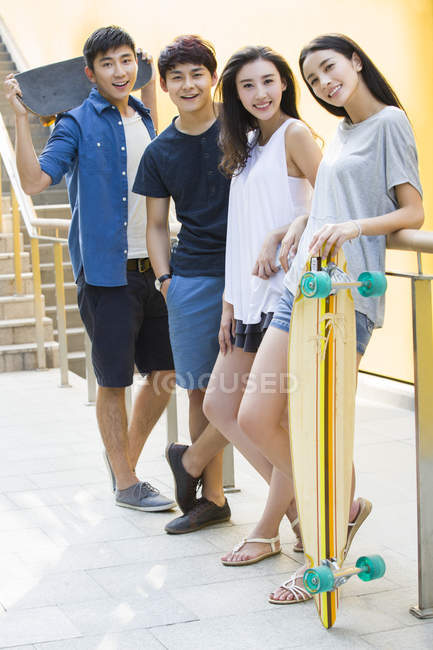 Chinese friends standing on street and holding skateboards — Stock Photo
