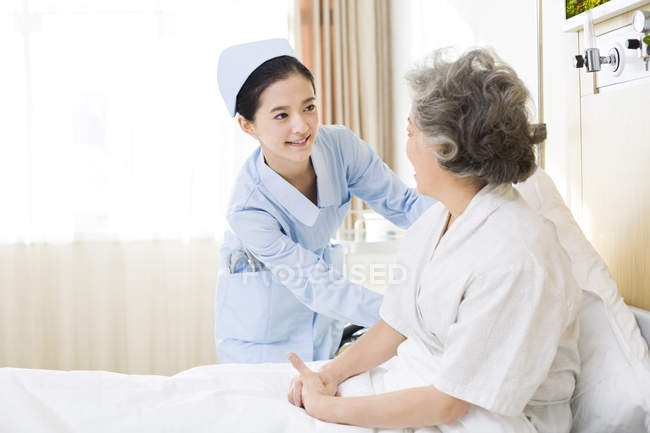 Китайская медсестра ухаживает за пожилой женщиной в больнице — стоковое фото