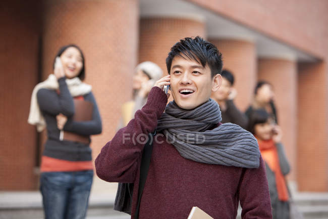 Chinese college students talking on phones on campus — Stock Photo