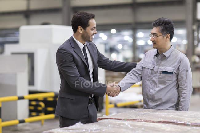 Unternehmer und Ingenieur beim Händeschütteln in Fabrik — Stockfoto