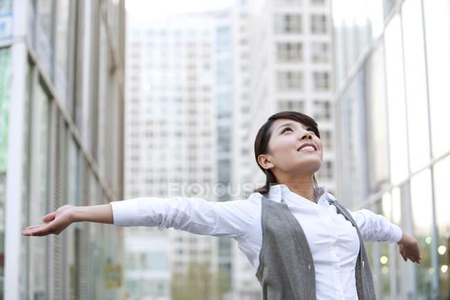 Китайская предпринимательница празднует с распростертыми в городе руками — стоковое фото