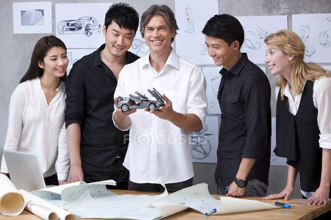 Car designers standing with model car — Stock Photo