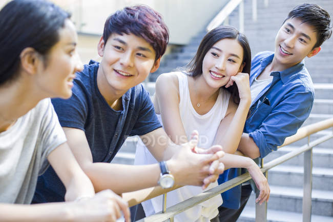 Chinese friends standing and leaning on balustrade — Stock Photo