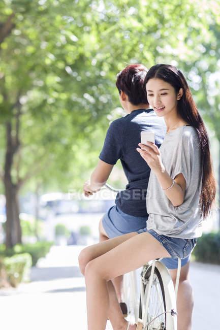 Femme chinoise assise sur petit ami vélo avec smartphone — Photo de stock