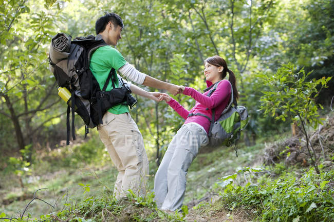 Chinese couple with backpacks holding hands and balancing in forest — Stock Photo