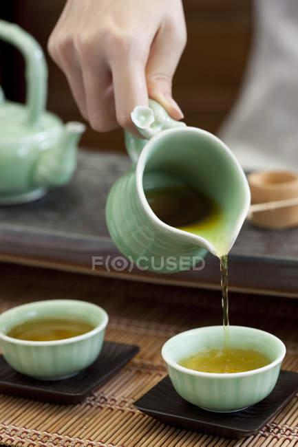 Gros plan des mains féminines, verser le thé dans les tasses à thé — Photo de stock