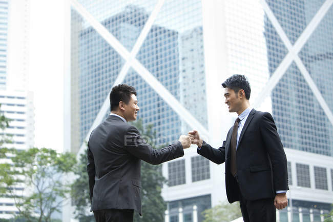Excited Chinese businessmen celebrating with fist bump on street — Stock Photo