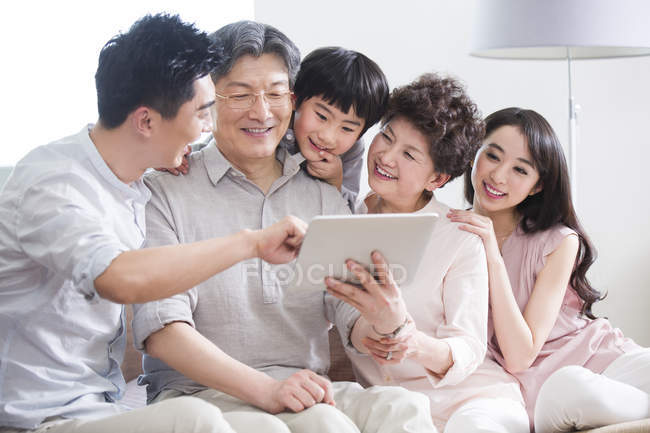Chinese family of three generations using digital tablet — Stock Photo