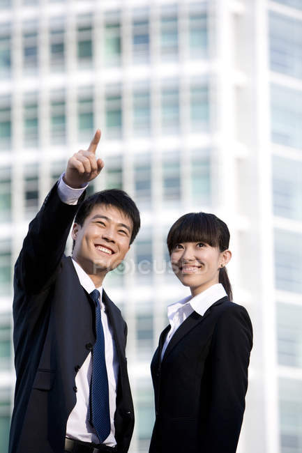 Chinese businessman pointing with businesswoman in front of skyscraper — Stock Photo
