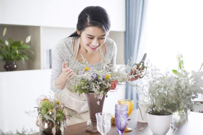 Mujer China de arreglo de flores en casa - foto de stock