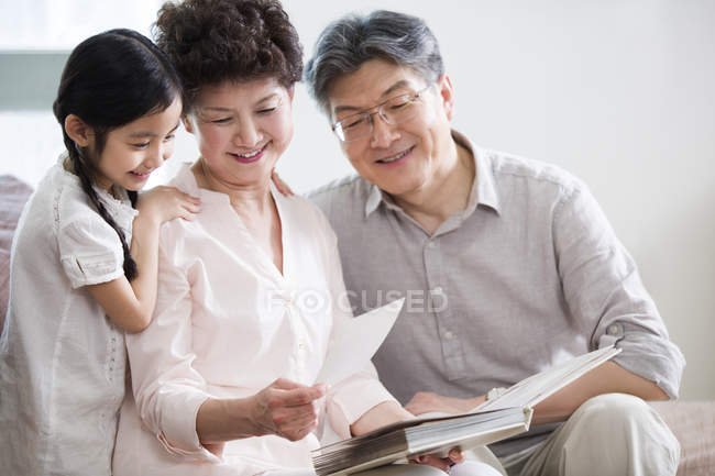 Chinese grandparents and granddaughter looking at photo album — Stock Photo