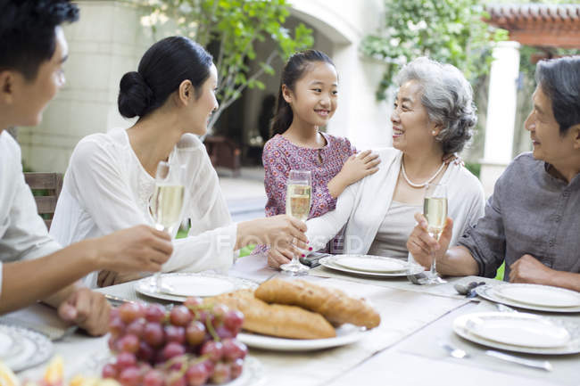 Chinese family talking at dining table in courtyard — Stock Photo