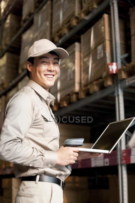Trabalhador do armazém chinês masculino com laptop e scanner — Fotografia de Stock