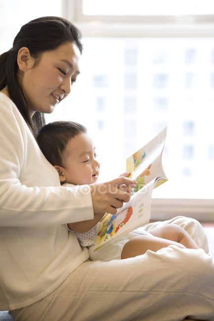 Китаянка, читающая с младенцем — стоковое фото