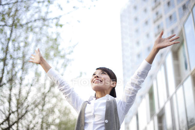 Chinese businesswoman celebrating with arms raised in city — Stock Photo