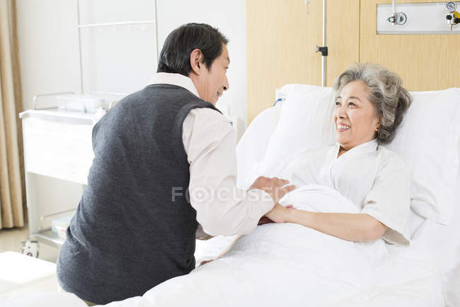 Chinese senior man visiting wife in hospital — Stock Photo