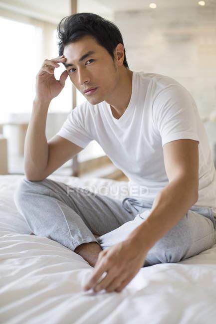 Hombre chino sentado en la cama y mirando en la cámara - foto de stock